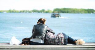 couple having rest on river embankment