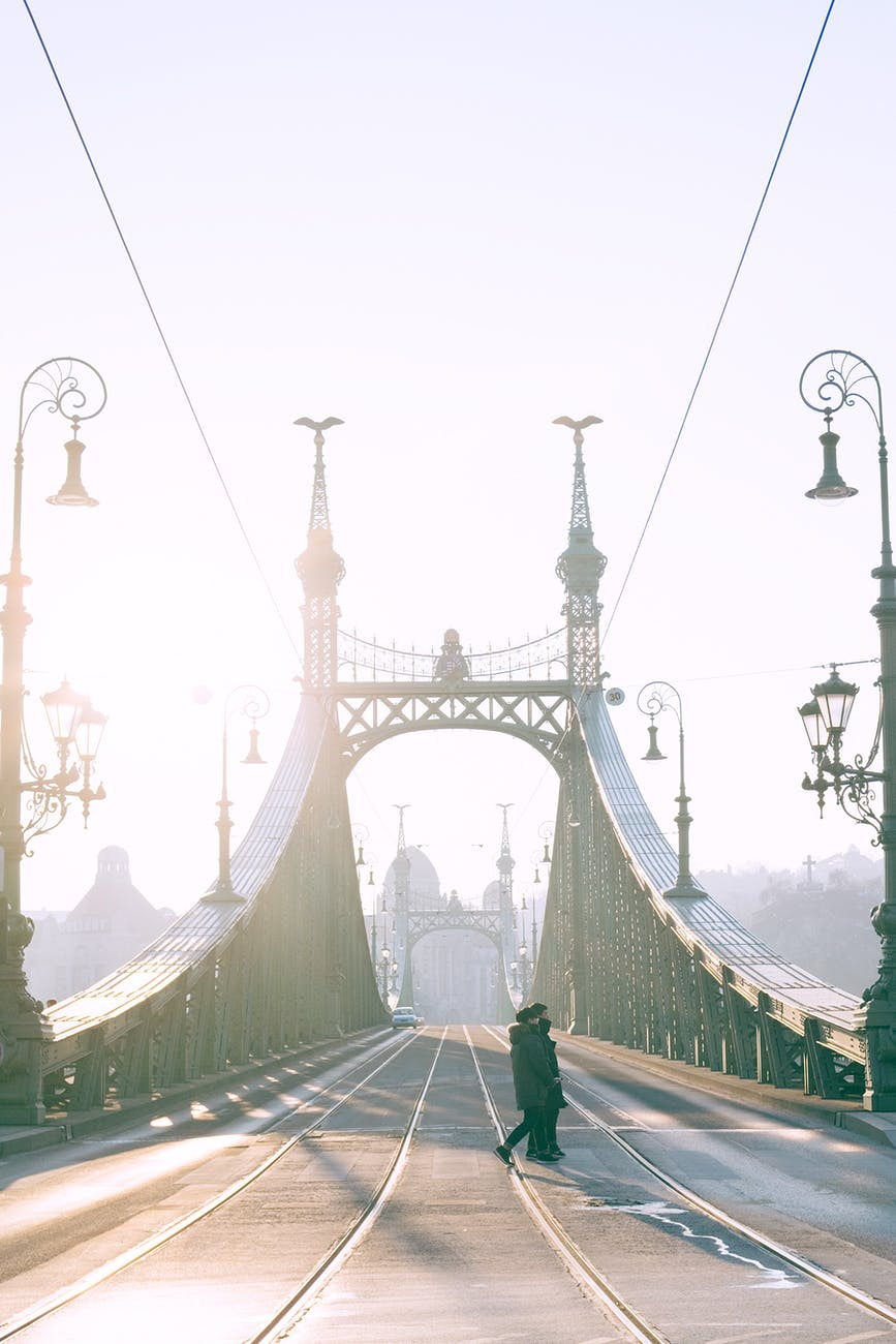 pedestrians crossing bridge with tramway rails against sunshine