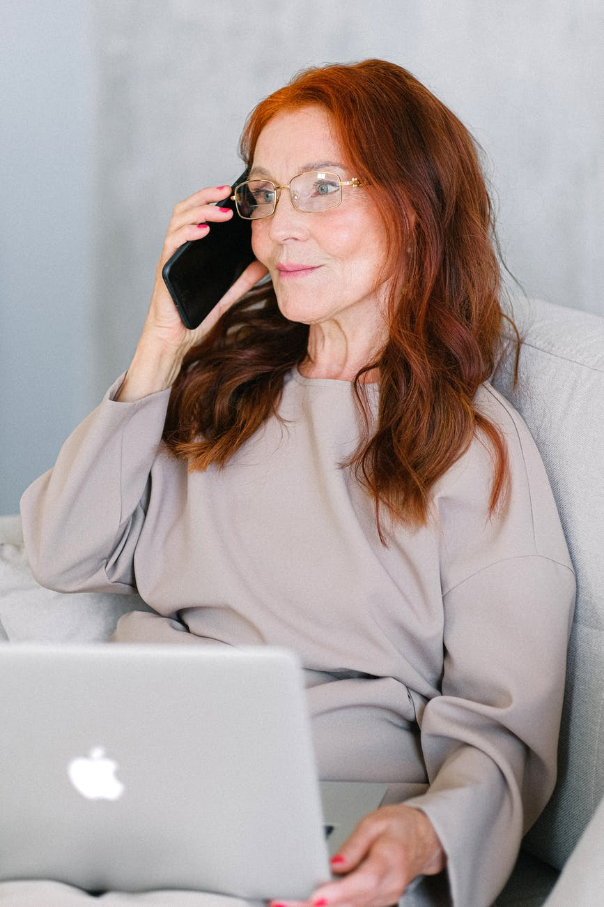 elderly woman with red hair talking on smartphone at laptop