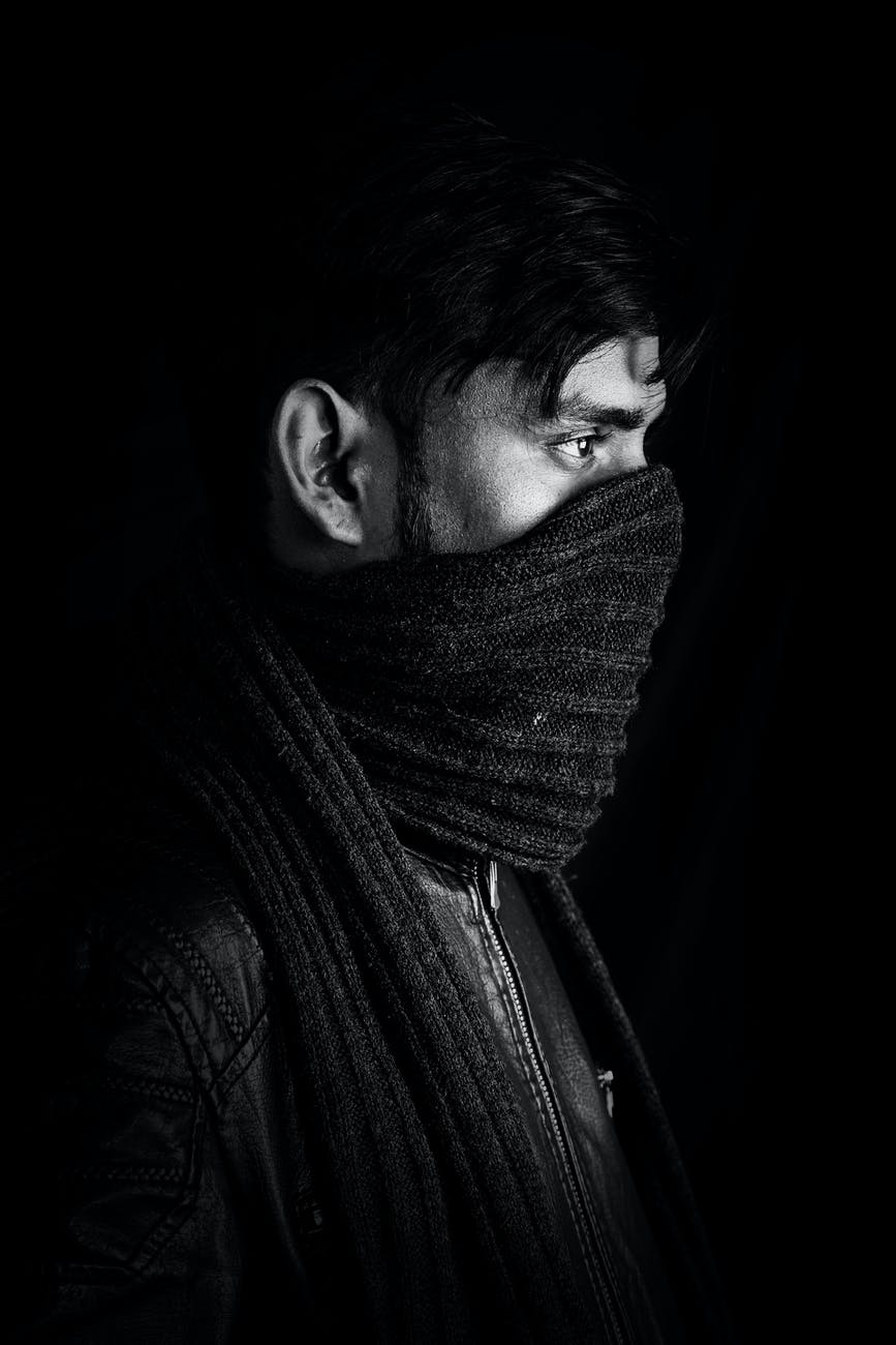ethnic man with scarf on face